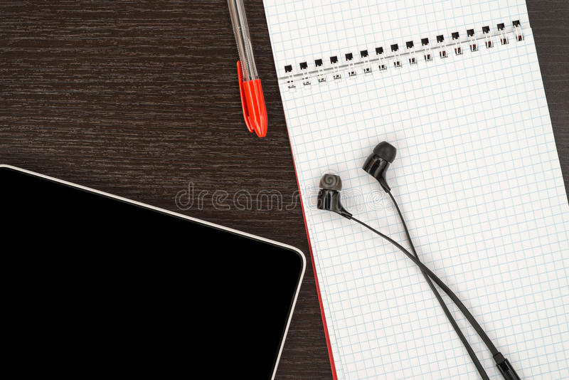 Tavola dell'ufficio con la compressa, le cuffie, la penna ed il taccuino immagine stock