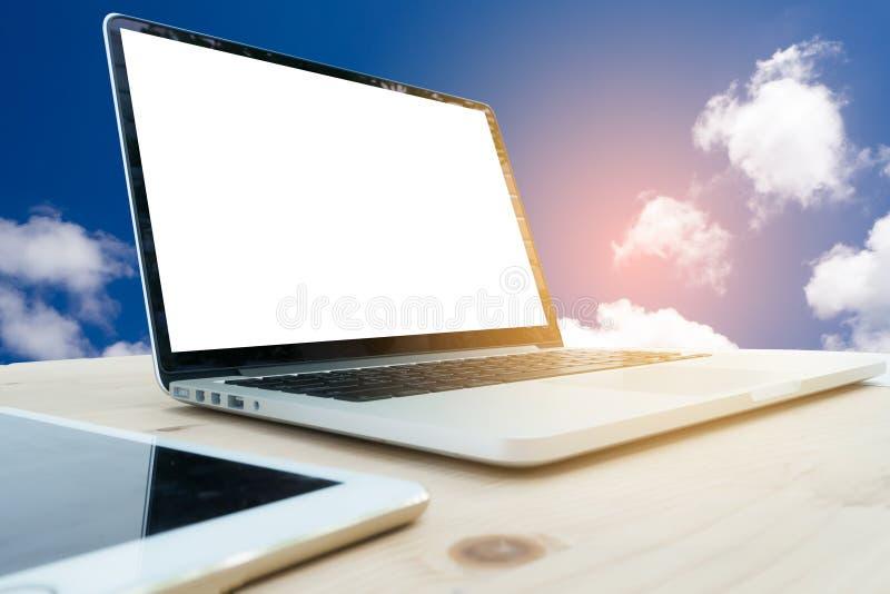 Tavola dell'ufficio con lo schermo in bianco sul backgrou del cielo nuvoloso e del computer portatile immagini stock