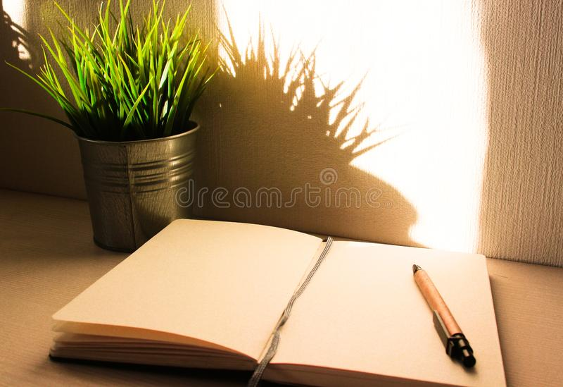 Tavola dell'ufficio di vista superiore, tavola con un taccuino aperto, un album, vetri, una pianta verde Colori saturati luminosi immagine stock libera da diritti