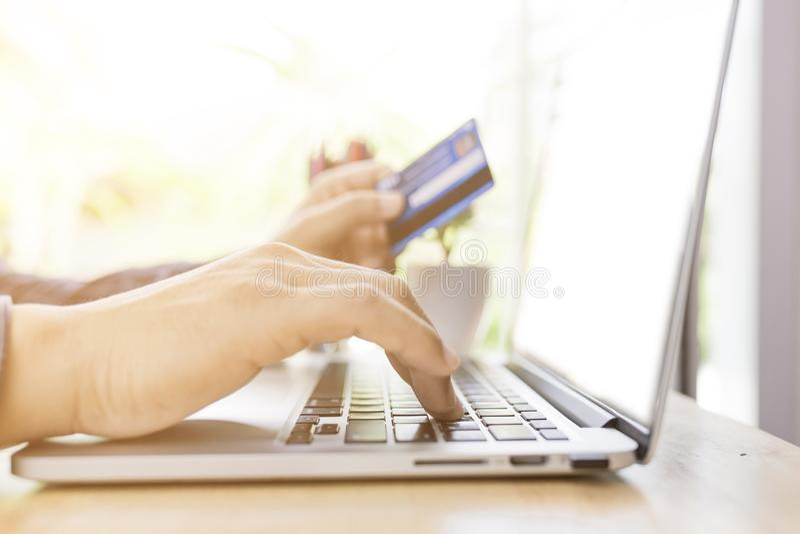 Tavola dell'uomo e taccuino di legno di seduta usando con la carta di credito per il pagamento online, le mani dell'uomo che teng fotografia stock
