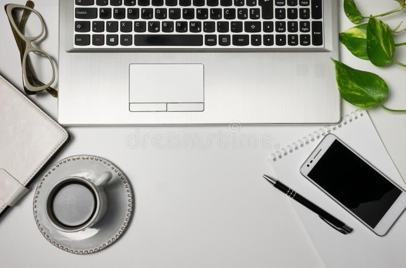 Tavola della scrivania di vista superiore con il computer portatile, blocco note, sellphone, tazza di caffè nero, pianta verde fotografia stock