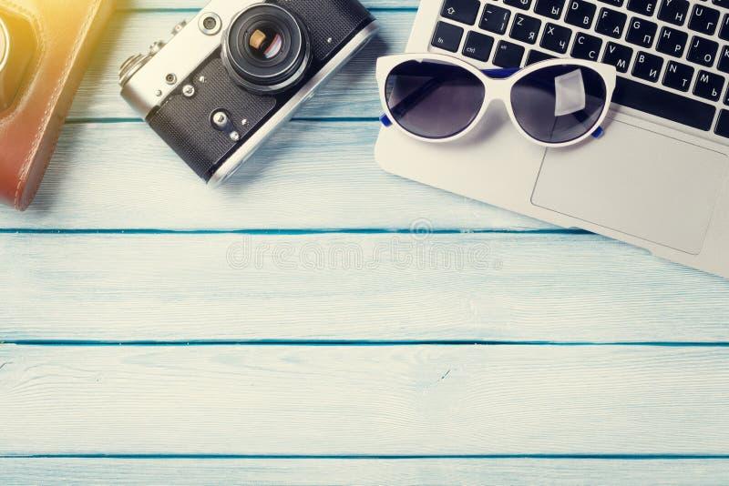 Tavola dello scrittorio con il computer portatile e la macchina fotografica fotografia stock libera da diritti