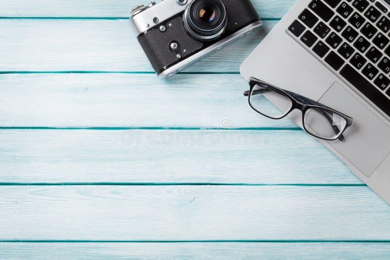 Tavola dello scrittorio con il computer portatile e la macchina fotografica immagine stock libera da diritti
