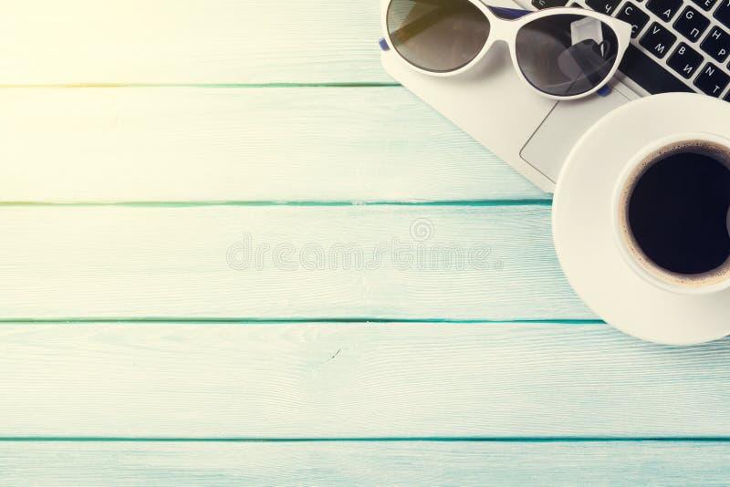 Tavola dello scrittorio con il computer portatile, il caffè e gli occhiali da sole fotografie stock libere da diritti