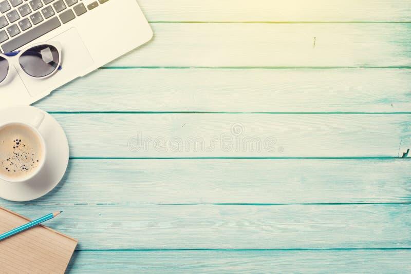Tavola dello scrittorio con il computer portatile, il caffè e gli occhiali da sole immagini stock libere da diritti
