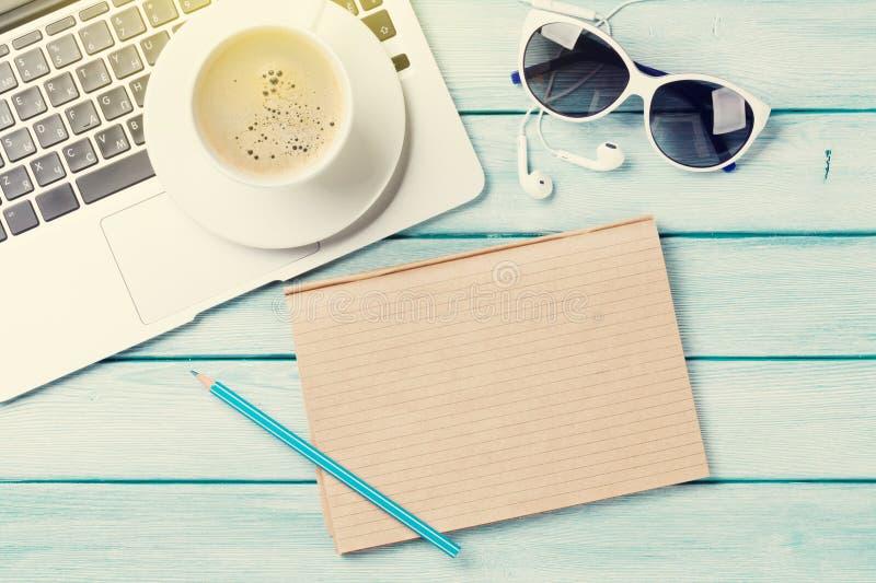 Tavola dello scrittorio con il computer portatile, il caffè e gli occhiali da sole immagine stock libera da diritti