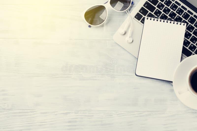 Tavola dello scrittorio con il computer portatile, il caffè e gli occhiali da sole immagine stock