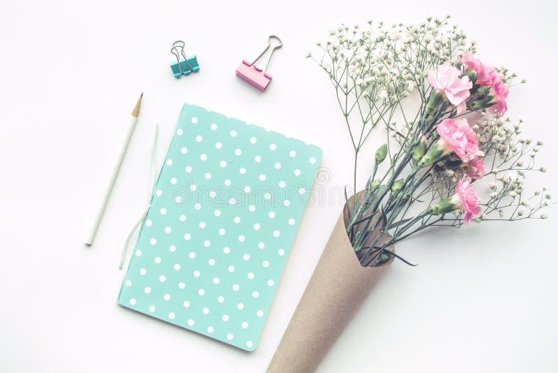 Tavola dello scrittorio del Ministero degli Interni con il blocco note, fiore su fondo bianco fotografia stock libera da diritti