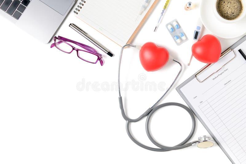 Tavola dello scrittorio di medico con lo stetoscopio ed il cuore rosso fotografia stock libera da diritti