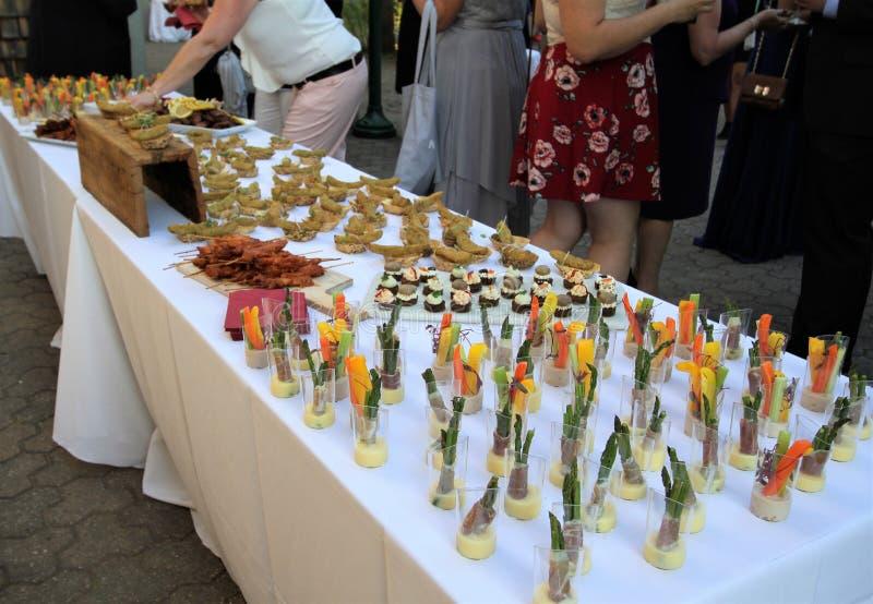 Tavola di buffet con le opere di verdure tagliate del ` di hors d su una tovaglia bianca fotografia stock libera da diritti