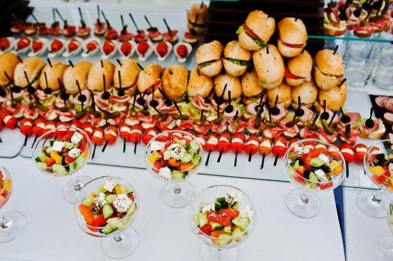 Tavola di buffet della ricezione con gli hamburger, gli spuntini freddi, la carne ed il sa fotografia stock libera da diritti