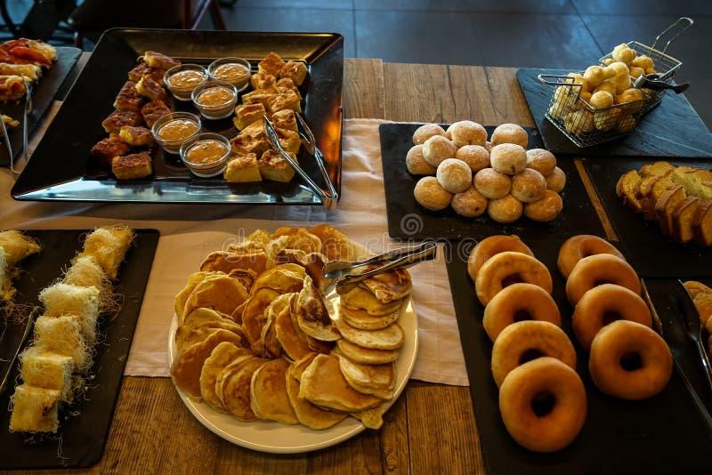Tavola di buffet greca della prima colazione in pieno con le varietà di pasticcerie, di panini, di pancake, di guarnizioni di gom fotografia stock libera da diritti