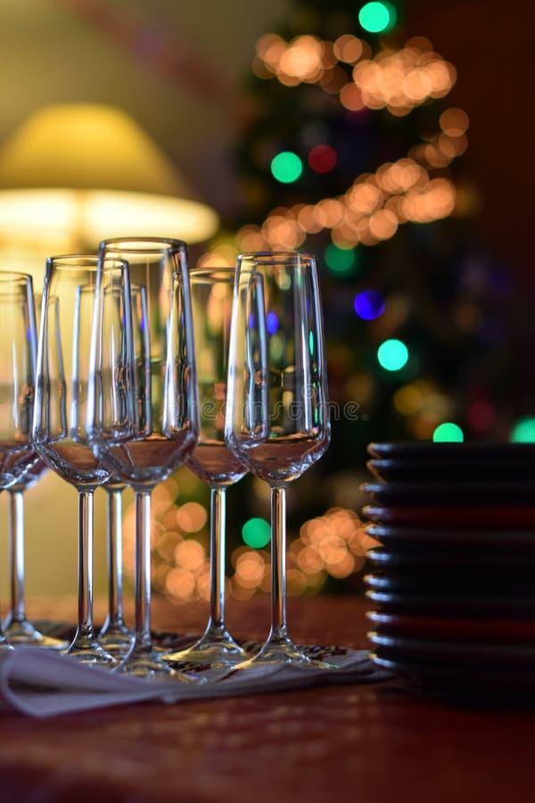 Tavola di celebrazione con i vetri del champagne ed i piatti impilati sul fondo dell'albero di Natale fotografia stock libera da diritti
