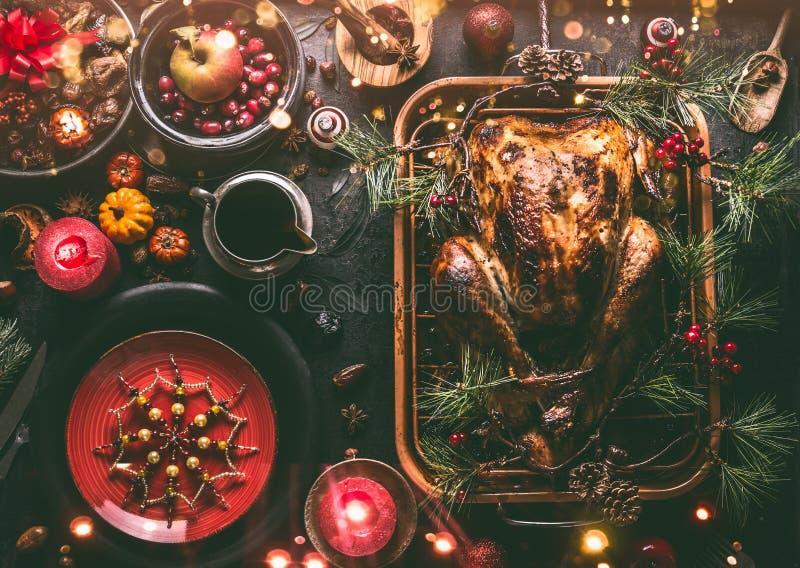 Tavola di cena di Natale con l'intero tacchino arrostito, farcito con i frutti secchi servito in pentola di torrefazione con sals fotografia stock libera da diritti