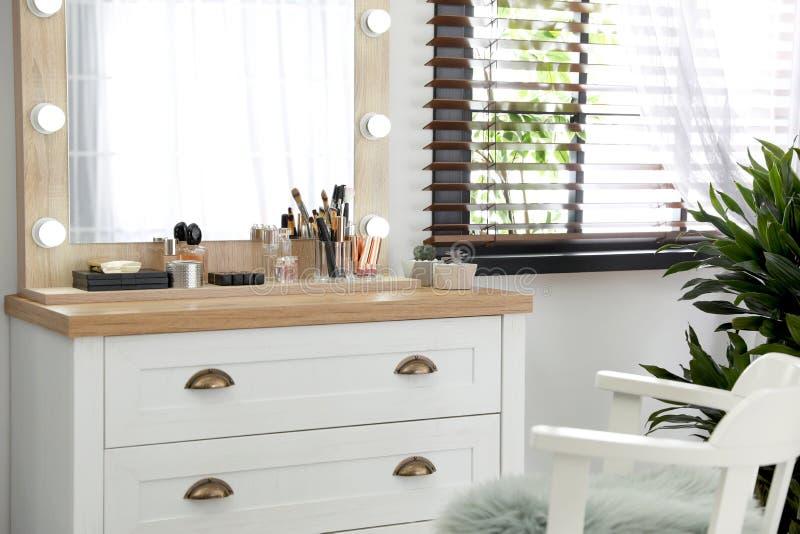 Tavola di condimento con i cosmetici e gli accessori di lusso nella sala immagine stock