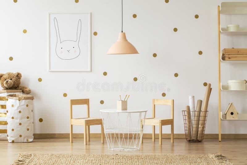 Tavola di cui sopra della lampada pastello fra le sedie in interi della stanza del ` s del bambino dell'oro immagini stock libere da diritti