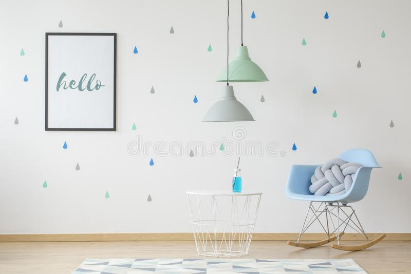 Tavola di cui sopra delle lampade nell'interno della stanza dei bambini con la sedia di oscillazione blu fotografia stock