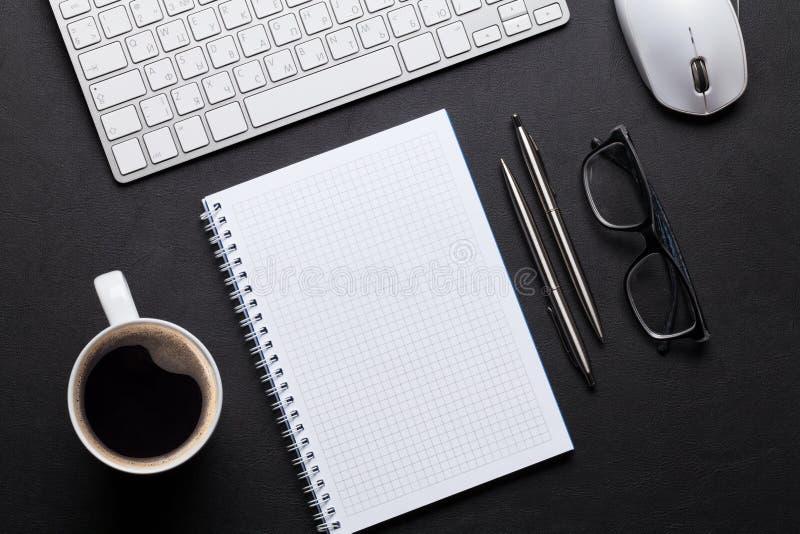 Tavola di cuoio dello scrittorio dell'ufficio con il blocco note, il pc ed il caffè fotografia stock