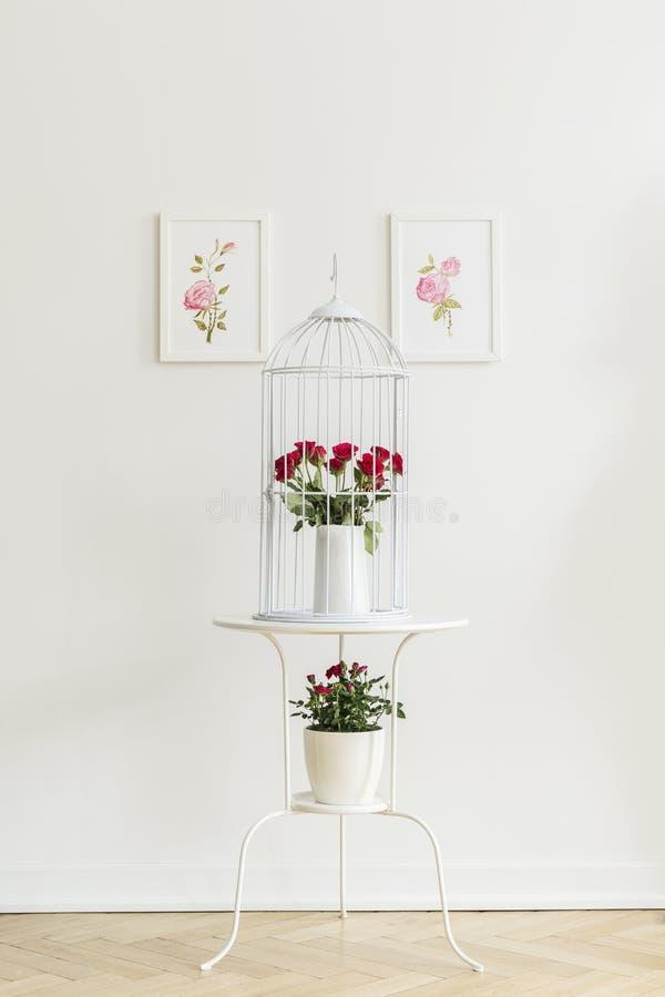 Tavola di estremità del metallo bianco con le rose rosse fresche che stanno sul herringbo fotografie stock