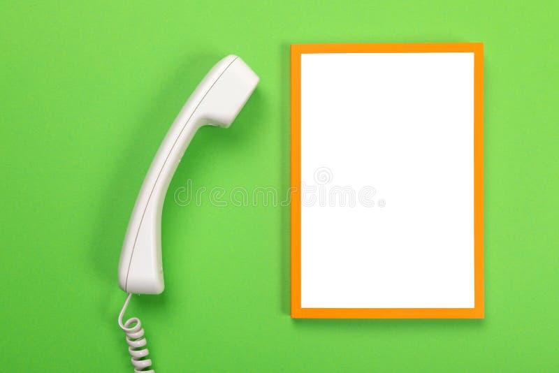 Tavola di funzionamento con il telefono e struttura con copyspace isolato su fondo verde fotografia stock