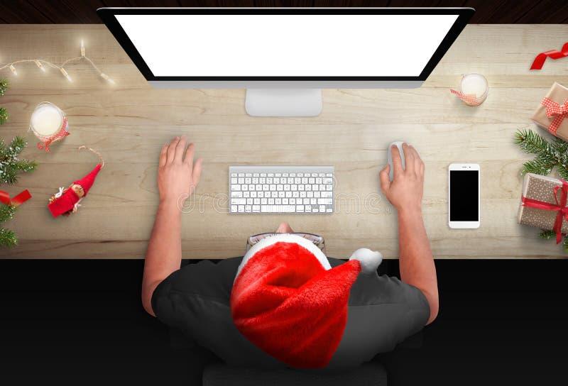 Tavola di funzionamento durante il Natale L'uomo lavora ad un computer immagini stock libere da diritti