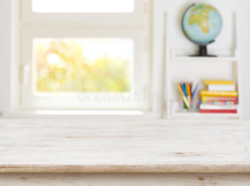 Tavola di legno con fondo vago della stanza e della finestra dei bambini immagine stock