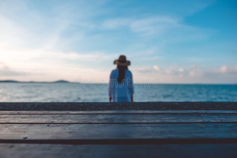 Tavola di legno con i precedenti del cielo blu e del mare e una donna della sfuocatura immagine stock