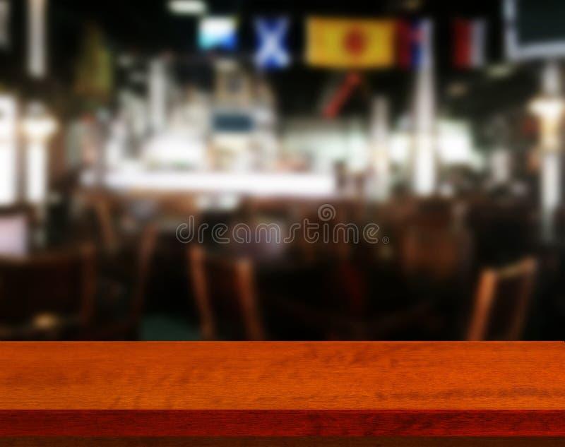 Tavola di legno con il caffè blured del fondo, per la vostra esposizione del montaggio o del prodotto della foto Spazio per la co immagine stock libera da diritti