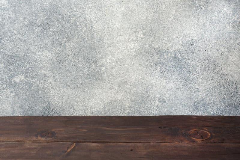 Tavola di legno con il fondo del muro di cemento, per la vostra esposizione del montaggio o del prodotto della foto, spazio per l immagini stock