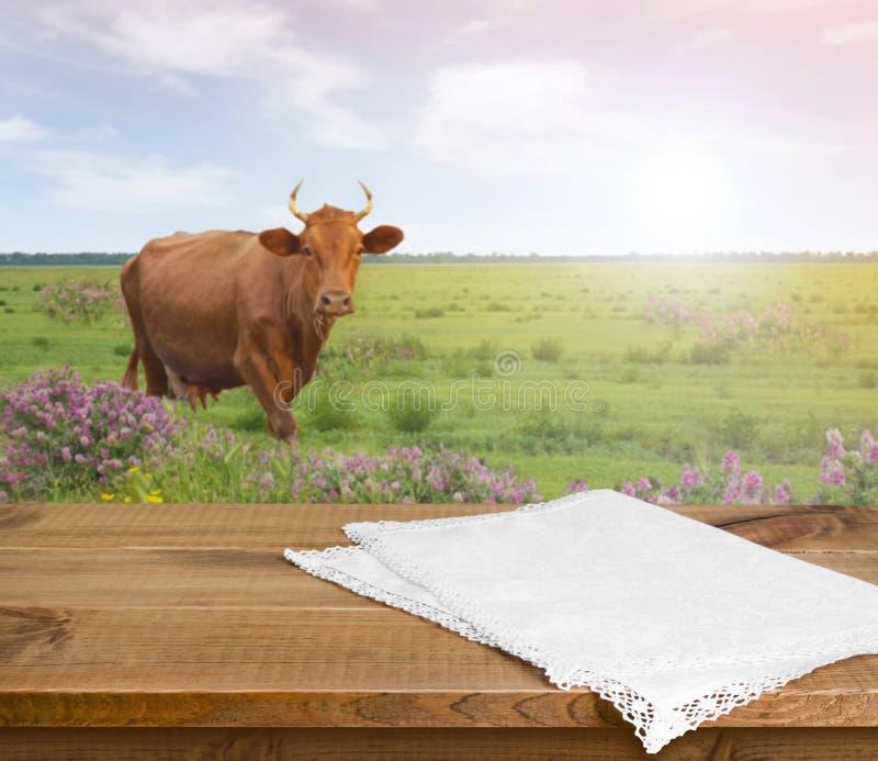 Tavola di legno con l'asciugamano di cucina sopra il fondo defocused del prato della mucca fotografia stock libera da diritti