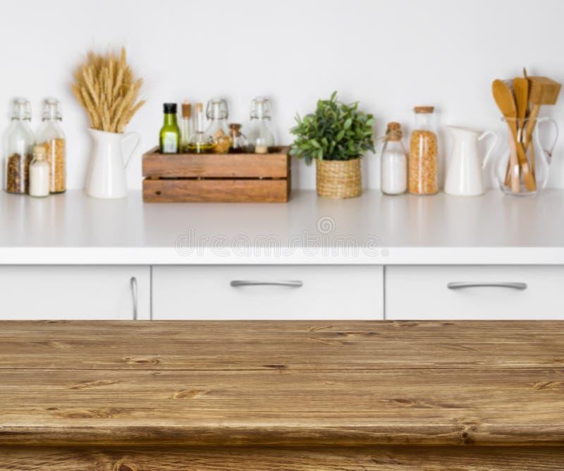 Tavola di legno di Brown con l'immagine del bokeh dell'interno del banco della cucina immagine stock
