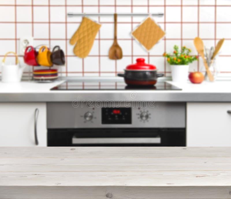 Tavola di legno di struttura sul fondo defocused del banco della cucina immagini stock
