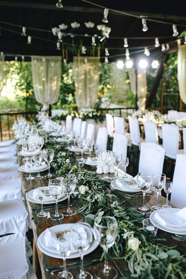 Tavola di legno elegante decorata di nozze in un gazebo con le lampade rustiche con l'eucalyptus ed i fiori, piatti della porcell immagini stock libere da diritti