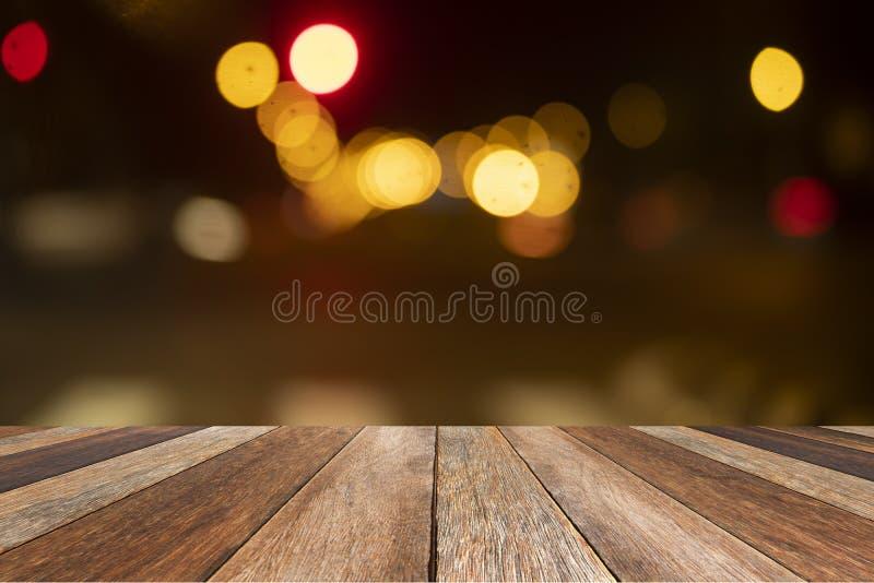 Tavola di legno di marrone nel fondo leggero del bokeh vago parte anteriore strutturato, per il prodotto di presentazione, falso  immagine stock