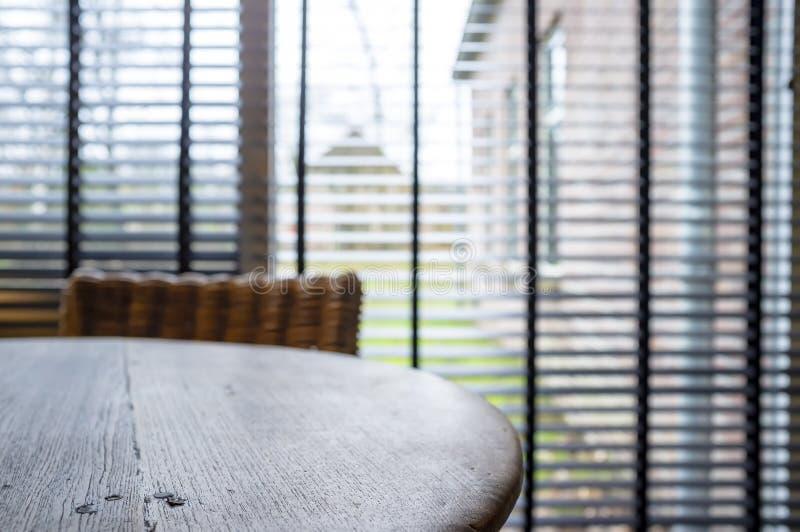 Tavola di legno rotonda semplice ed elegante in un interno domestico accogliente, contro lo sfondo di grandi finestre con i ciech fotografia stock libera da diritti