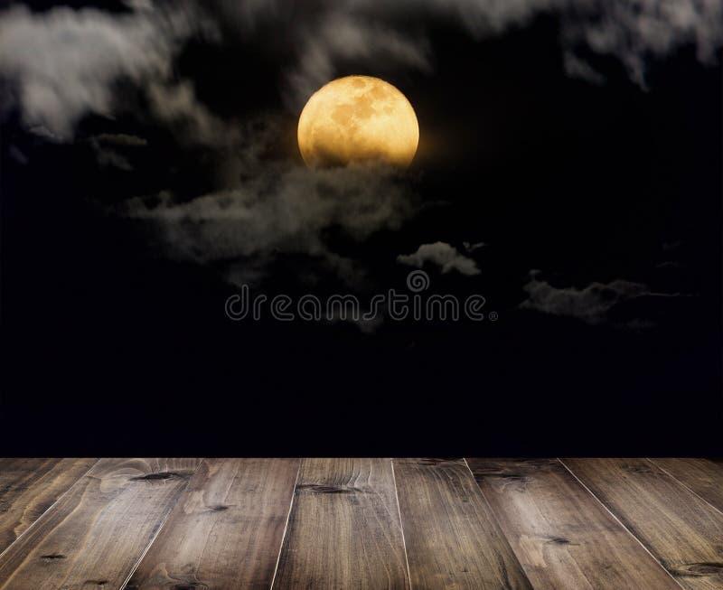 Tavola di legno sopra la luna piena con le nuvole alla notte fotografie stock