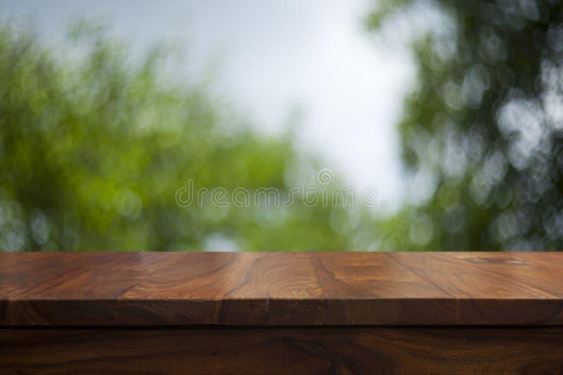 Tavola di legno superiore vuota e fondo vago floreale fotografie stock libere da diritti
