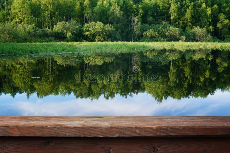 Tavola di legno vuota contro lo sfondo del paesaggio di estate immagini stock libere da diritti
