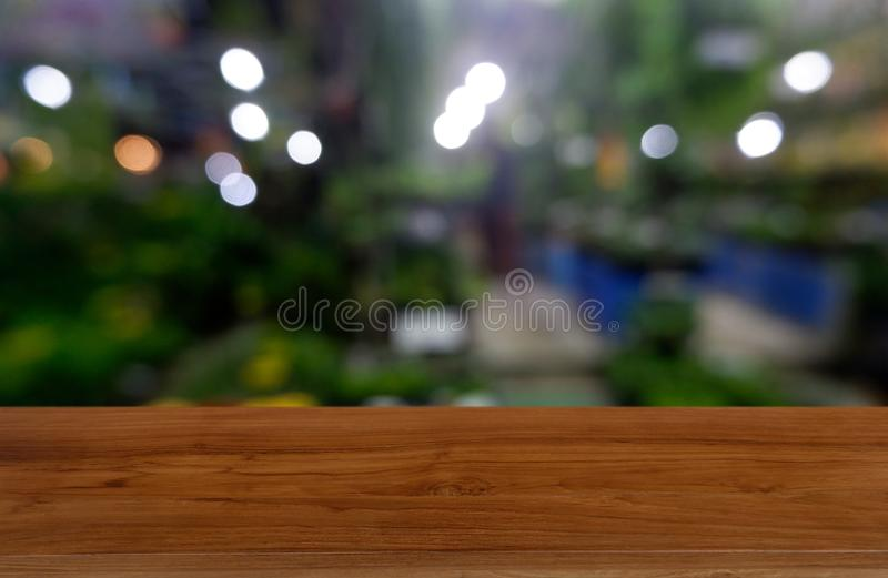Tavola di legno vuota davanti a verde vago astratto del fondo della casa e del giardino Per l'esposizione del prodotto del montag fotografie stock