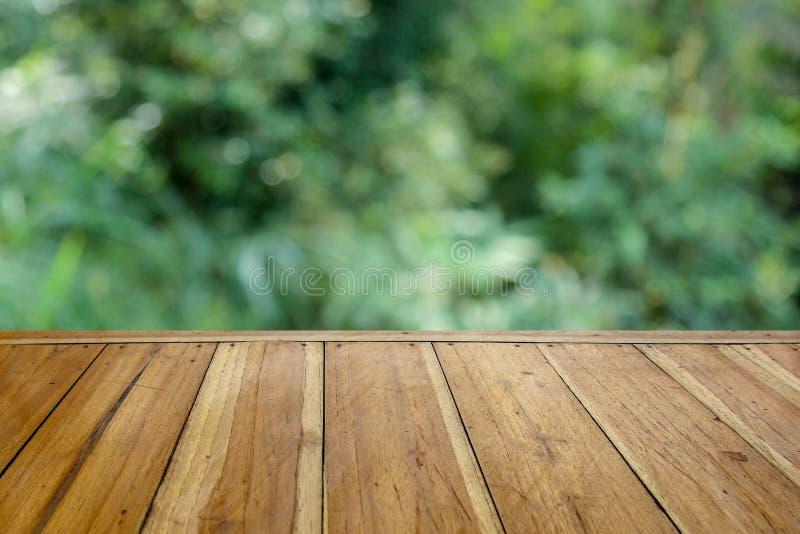 Tavola di legno vuota per il vostro prodotto ed offuscare sfondo naturale fotografia stock libera da diritti