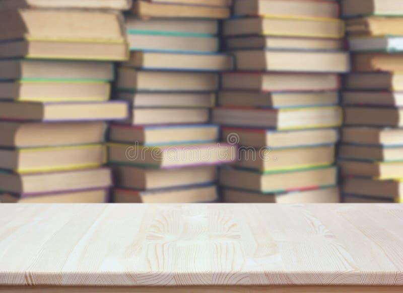 Tavola di legno vuota su fondo vago dei libri Scrittorio vuoto fotografie stock