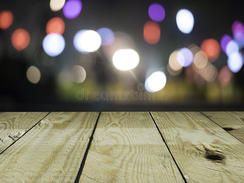 Tavola di legno vuota sul fondo variopinto del bokeh, uso per l'esposizione del prodotto fotografia stock