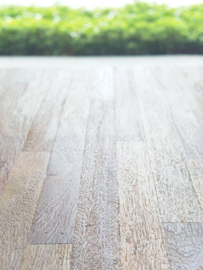 Tavola di legno vuota sul fondo verde astratto del giardino della sfuocatura di mattina Per l'esposizione del prodotto del montag fotografie stock