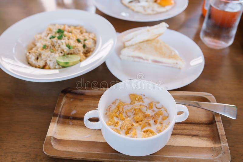 Tavola di prima colazione messa di cereale riempito di latte in ciotola e piatto di legno fotografia stock libera da diritti
