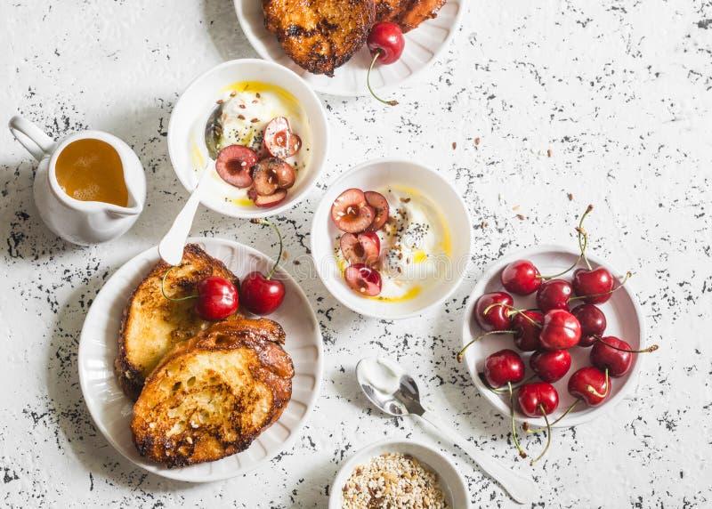 Tavola di prima colazione Yogurt greco con le ciliege ed il pane tostato francese sulla tavola bianca, vista superiore del carame fotografie stock