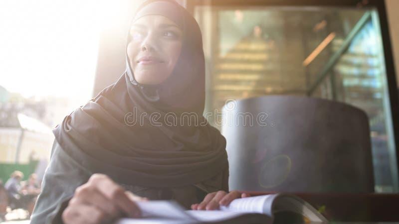 Tavola di seduta sorridente del caffè della donna araba con il libro che studia, istruzione, svago immagine stock