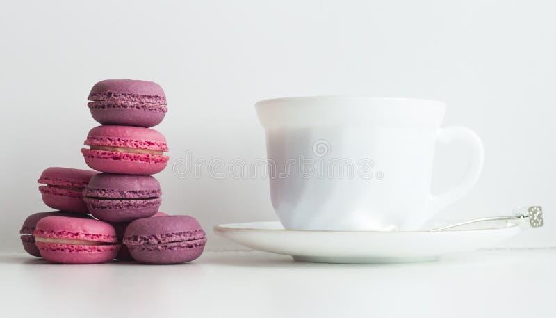 Tavola di tè di pomeriggio con i macarons variopinti e una tazza di tè fotografie stock libere da diritti