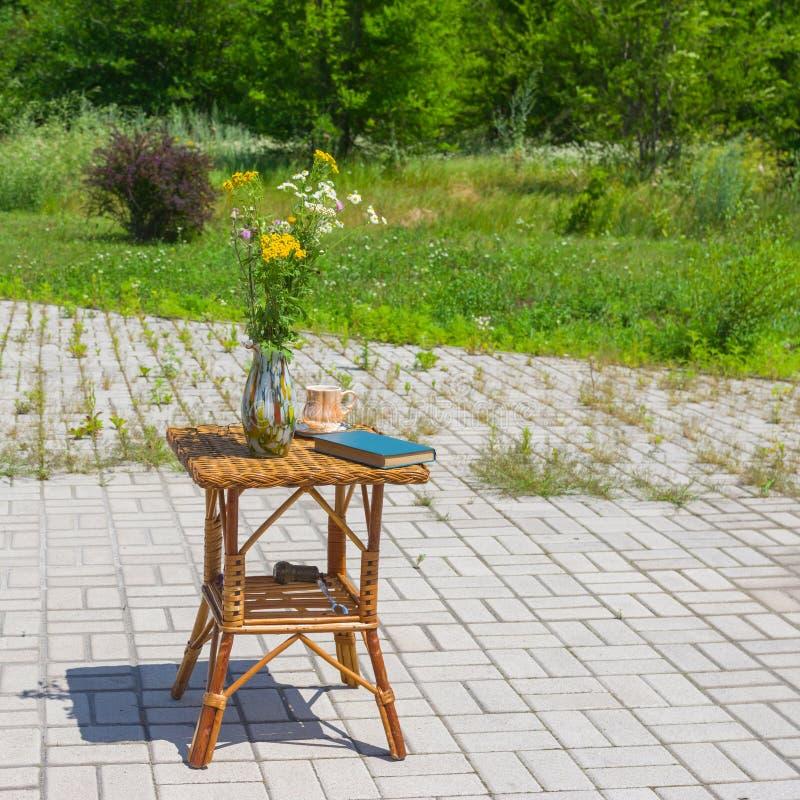 Download Tavola Di Vimini Con Il Mazzo Dei Fiori Selvaggi In Un Vaso Fotografia Stock - Immagine di piccolo, sunny: 56877446