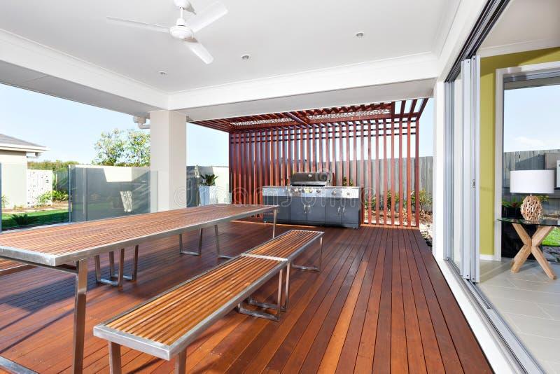 Tavola e banchi di legno lunghi con il gabinetto moderno della griglia in una LU immagine stock
