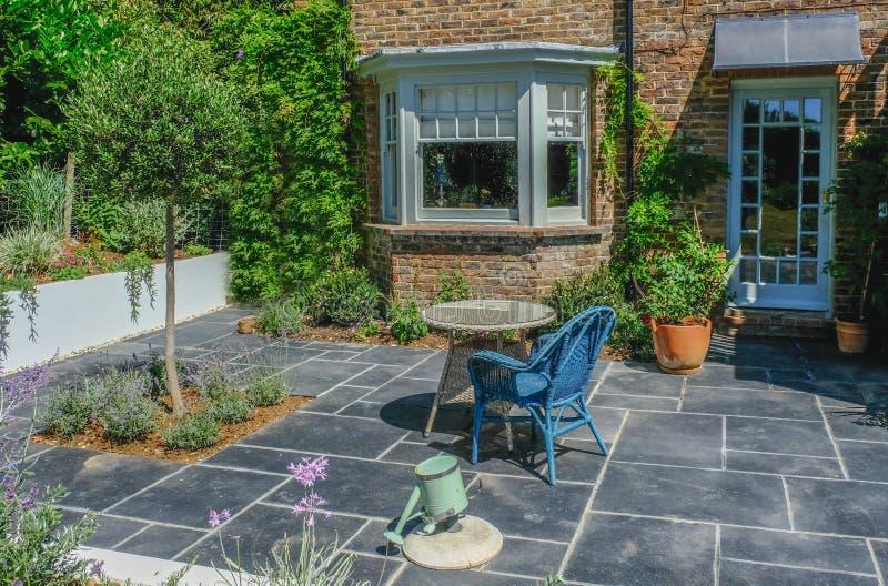 Tavola e sedia di vimini su un'area vuota del patio immagini stock